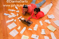Couple paying bills or doing their personal tax return. Couple is laying on floor with laptop and surrounded by bills and receipts.